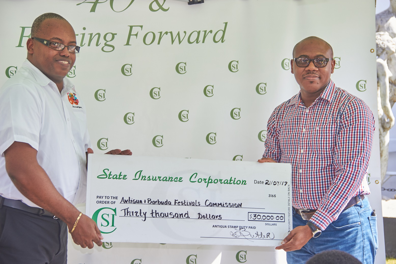 ABFC Chairman Maurice Merchant accepts cheque from SIC Financial Controller Andre Knight